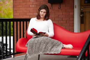 Jen reading a book on a red couch with Interwoven Blanket on her lap